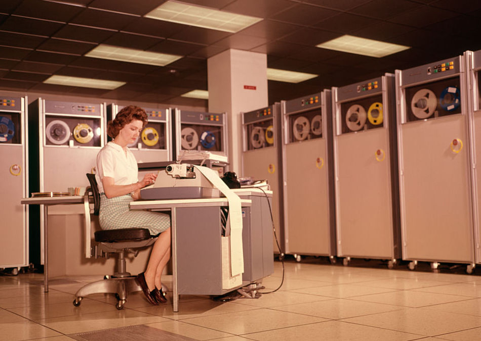 A woman enters data into a 1960s B-5000 computer surrounded by reels of magnetic tape units.