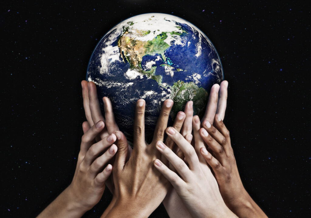 Diverse set of hands holding up the globe on a black background