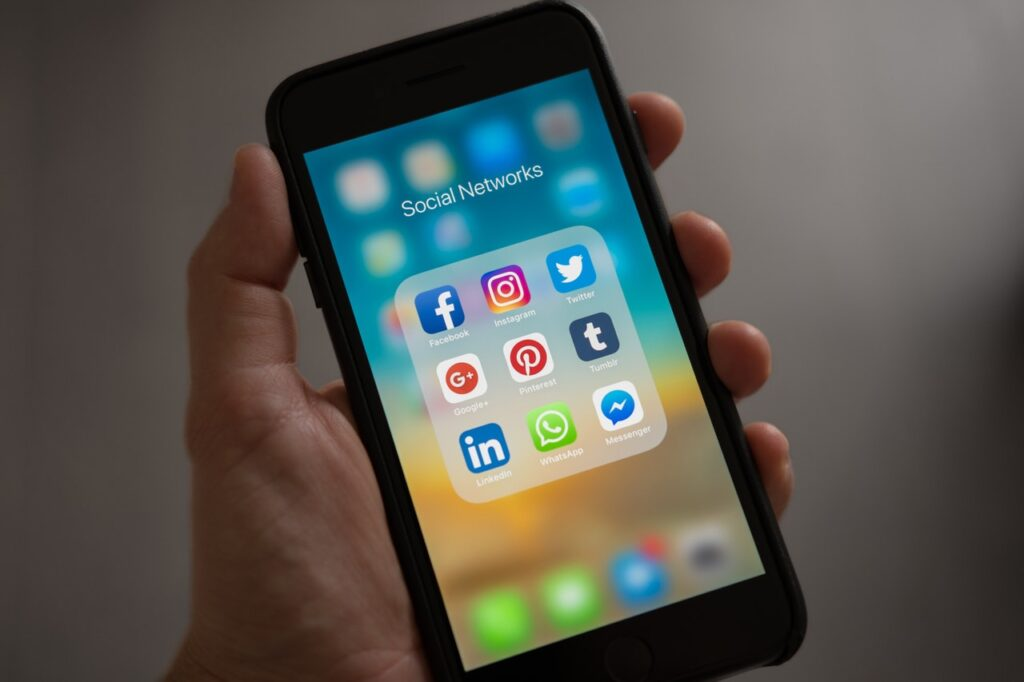 Hand holding mobile phone with screen showing 3 rows of social media icons